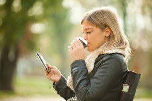 Young woman using tablet in park, drinking coffee to go